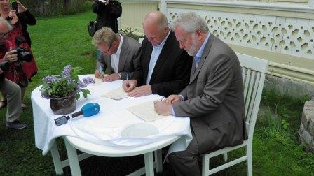 Fylkesordfører Bjørgulv Sverdrup Lund, ordfører Jan Dukene og riksantikvar Jørn Holme signerer kjøpsavtalen på Furøya