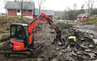 Restaurering av gamle steinmurer er et møysommelig arbeid. Eystein Greibrokk gjør handarbeidet, mens Anders Oppegaard styrer gravemaskinen. Foto: Asbjørn Aanonsen
